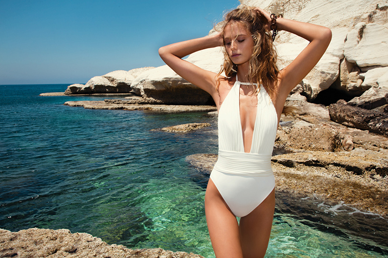 A deep plunge maillot by Gottex Cruise with halter neckline is accented with tuxedo pleats and cummerbund waist details.