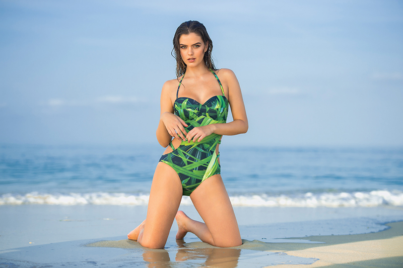 Lush palm leaves pop against a solid navy ground in a twist-bra bandeau monokini with dual side-strap detail by Leonisa.